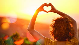 Woman Making Heart Shape Around Sun With Hands